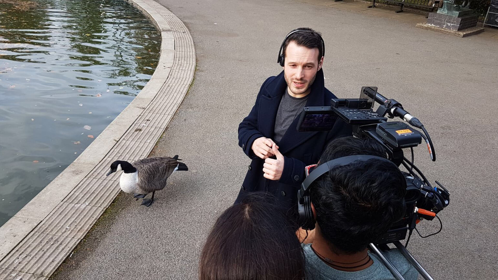 e4 presenter aaron calvert being interviewed about hypnosis project by a pond about stage entertainment